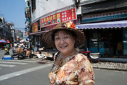A woman in a floral sun hat.
