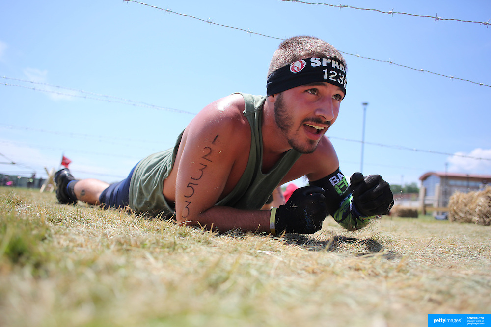 Jack Ziems in action at the barbed wire crawl obstacle during the Reebok Spartan Race. Mohegan Sun, Uncasville, Connecticut, USA. 28th June 2014. Photo Tim Clayton
