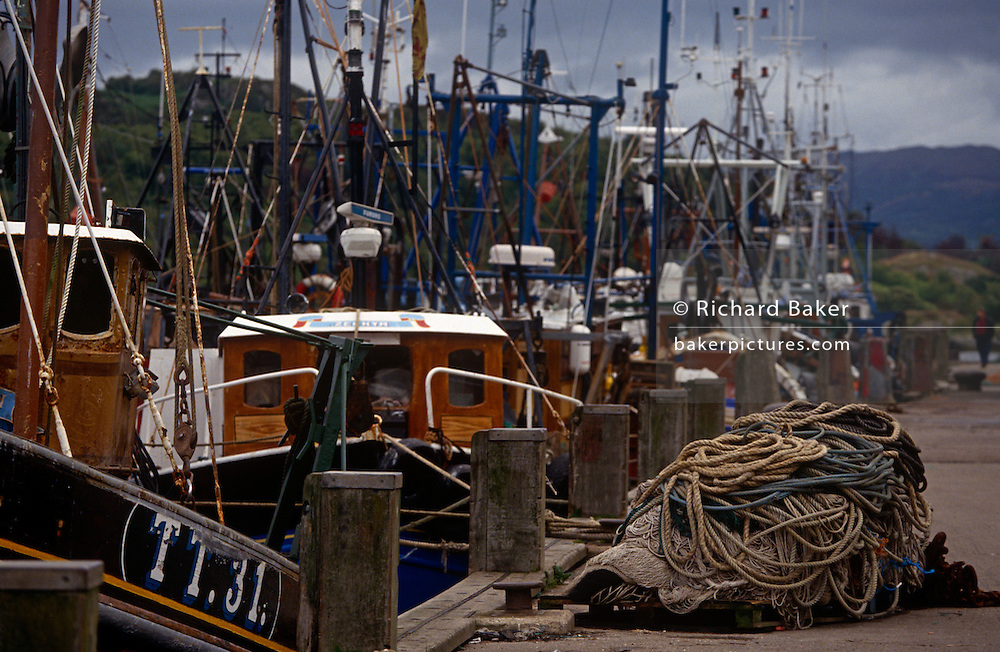 Fishing boats are moored up on the quayside at the village of Tarbert on the Mull of Kintyre, Scotland.