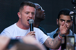 London, UK. 14 May, 2019. Former English Defence League leader Tommy Robinson addresses his supporters outside the Old Bailey following a hearing during which two High Court judges declared that fresh proceedings may be brought against him for an alleged contempt of court over the filming of people involved in a criminal trial.