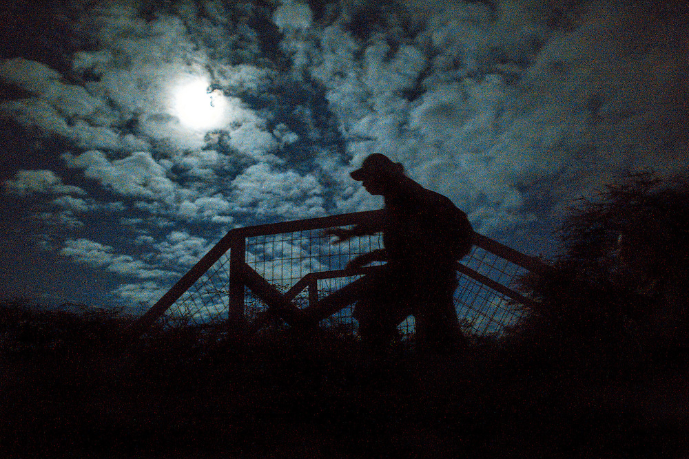 4:43am Brother Nolan leads group across bridge to Kaupoa trail in West Molokai.  This image lit only by moonlight.