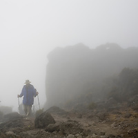 Africa, Tanzania, Kilimanjaro National Park, (MR) Climbing party hiking through dense fog toward Karanga Camp (13000')  on climbing expedition