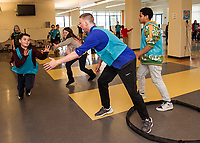 """Nike athlete Will McLean reaches for a tag to get out of jail during """"capture the football"""" with the Nike Ambassador after school program at Laconia Middle School on Thursday afternoon.  (Karen Bobotas/for the Laconia Daily Sun)"""