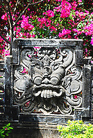 Stone temple ornament surrounded by colorful vegetation in Bali, Indonesia.