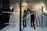 Retail window dressers prepares the small features in a new display at the London brance of department store Harvey Nichols.