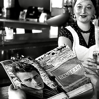 Young woman in bar drinking wine and reading a magazine