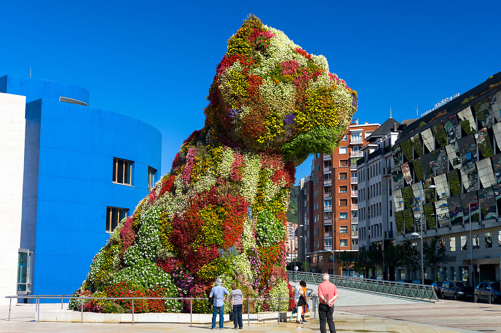 Tourists at Puppy by Jeff Koons floral art in dog form at Guggenheim Museum by Silken Gran Hotel Domine in Bilbao, Spain