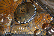 View from below of interior and domes showing Islamic elements in the ceiling,  Hagia Sophia, 532-37, by Isidore of Miletus and Anthemius of Tralles, Istanbul, Turkey. Hagia Sophia, The Church of the Holy Wisdom, has been a  Byzantine church and an Ottoman mosque and is now a museum. The current building, the third on the site, commissioned by Emperor Justinian I, is a very fine example of Byzantine architecture. The historical areas of the city were declared a UNESCO World Heritage Site in 1985. Picture by Manuel Cohen.