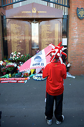 LIVERPOOL, ENGLAND - Saturday, April 11, 2009: A young Liverpool supporter at the memorial to the 96 supporters who lost their lives at the Hillsborough Stadium Disaster on 15th April 1989. Twenty years on the victims families are still waiting for justice as none of the police officers responsible for the deaths of so many supoporters have ever been brought to justice. (Photo by: David Rawcliffe/Propaganda)