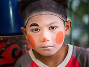 "14 MAY 2015 - BANGKOK, THAILAND:    A child Chinese opera performer backstage before a show at the Pek Leng Keng Mangkorn Khiew Shrine in the Khlong Toey slum in Bangkok. Chinese opera was once very popular in Thailand, where it is called ""Ngiew."" It is usually performed in the Teochew language. Millions of Chinese emigrated to Thailand (then Siam) in the 18th and 19th centuries and brought their culture with them. Recently the popularity of ngiew has faded as people turn to performances of opera on DVD or movies. There are still as many 30 Chinese opera troupes left in Bangkok and its environs. They are especially busy during Chinese New Year and Chinese holiday when they travel from Chinese temple to Chinese temple performing on stages they put up in streets near the temple, sometimes sleeping on hammocks they sling under their stage. Most of the Chinese operas from Bangkok travel to Malaysia for Ghost Month, leaving just a few to perform in Bangkok.      PHOTO BY JACK KURTZ"