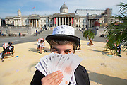 UNITED KINGDOM, London: 12 May 2016 Vicky, from Christian Aid, takes part in a campaign to increase pressure on David Cameron and other world leaders to clamp down on tax dodging. Trafalgar Square was turned into a tropical 'tax haven' this morning as volunteers  dressed in business suits and bowler hats organised by Oxfam, ActionAid and Christian Aid. <br /> Rick Findler / Story Picture Agency