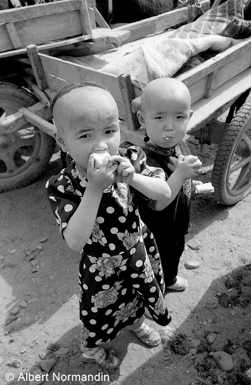 Children with shaven heads in market