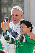 Child takes a selfie with Pope Francis as he arrives in St. Peter's Square for his weekly general audience, at the Vatican, Wednesday, March 14, 2018.