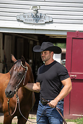 hot cowboy with a horse on a ranch