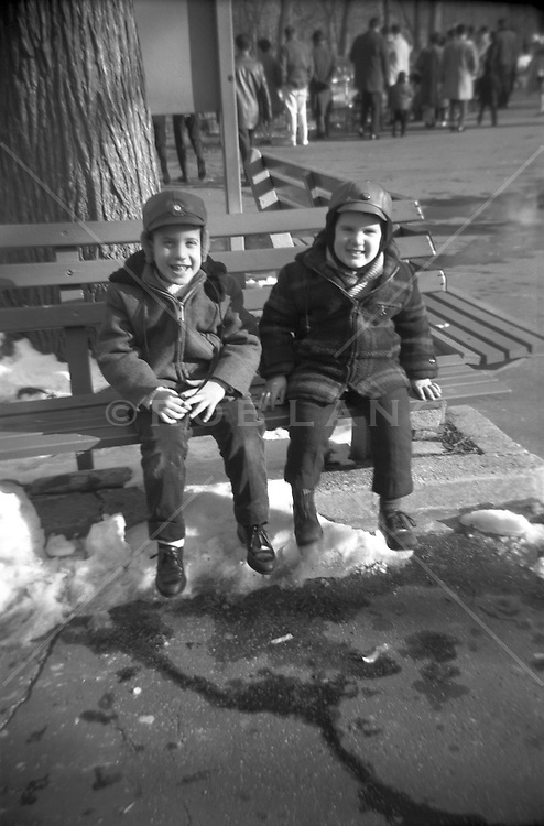 winter scene of two boys on a park bench in New York