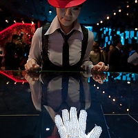 MACAU - FEBRUARY 01:  Staff member poses for media in front of the famous white rhinestone glove worn by Michael Jackson at the 1983 Motown 25 Television Special during which he premiered the moonwalk to the world during the opening ceremony of the MJ Gallery at Ponte 16 Resort-Macau on February 1, 2010 in Macau.  Photo by Victor Fraile / studioEAST