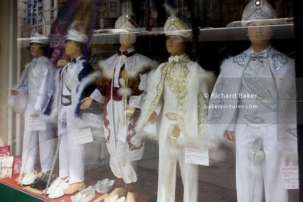Five boy mannequis display ceremonial costumes for special occasions in the window of a clothing supplier in a southern suburb of Berlin, Germany.