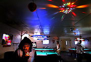 "Raul, 25, has a beer and a smoke inside a Saluda, South Carolina pool hall, Friday, May 19, 2006. He came to the U.S. illegaly from Veracruz, Mexico seven years ago and hasn't seen his family since. ""I can't even remember what they look like,"" he said. Traveling alone, Raul made his way to South Carolina from California and has been working at Amick Farms processing chickens. ""I don't think people realize how hard life can be here,""he said. ""I'm ready to go back. I'm done. I've made up my mind."""