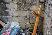 Discarded cross with a deceased person's name lying in a communal cemetery bin of a rural village in the Kozjansko Regional Park, on 24th June 2018, in Prevorje, Slovenia.