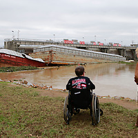 Thomas Wells | BUY AT PHOTOS.DJOURNAL.COM<br /> Mike Davis and his mother, Pat, from Ethelsville Ala., see the results of two barges that broke loose from the Raymond D. Lucas Memorial Port in Clay County on Saturday and struck the John C. Stennis Lock and Dam in Columbus where one of the barges sunk on Monday.