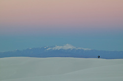 USA, New Mexico, White Sands National Monument. A couple walks over a dune of white sand at sunset. Credit as: © Josh Anon / Jaynes Gallery / DanitaDelimont.com