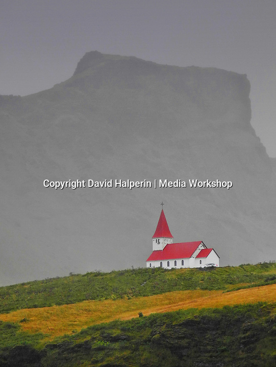 Front: red-roofed church on a hill. Rear: mountain crag