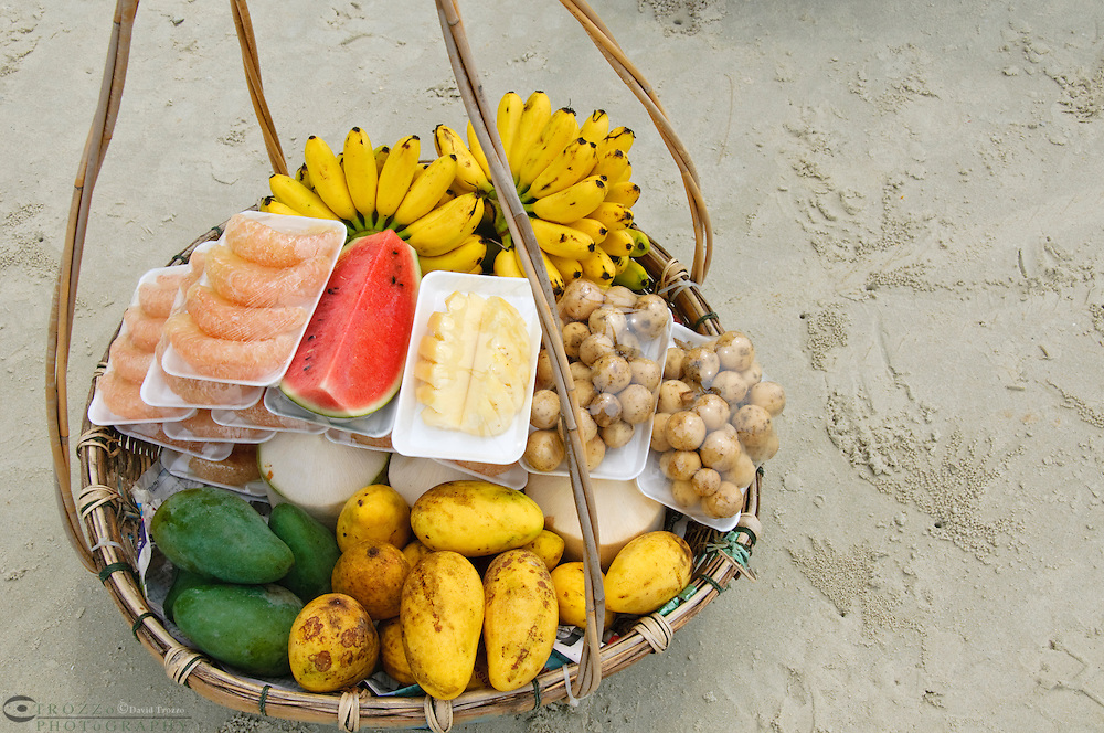 Beach vendor's basket filled with tropical fruits, bananas, mango, melon pummalo, coconut, and lumyai, Koh Samet, Thailand