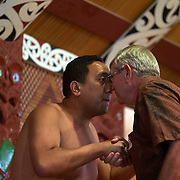A Maori cultural performer greets a member of the public with a hongi, a traditional Maori greeting in New Zealand,  which is done by pressing one's nose to another person at an encounter...The traditional hongi greeting took place at the  Maori Cultural Performances at Te Puia, Maori Arts and Crafts Institute, Te Whakarewarewa Thermal Valley, Rotorua, New Zealand..Te Puia is the premier Maori cultural centre in New Zealand - a place of gushing waters, steaming vents, boiling mud pools and spectacular geysers. Te Puia also hosts National Carving and Weaving Schools and  daily maori culture performances including dancing and singing. Rotorua, 8th December 2010 New Zealand.