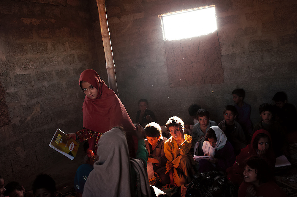 Pakistan/ Afghan refugees/ Students at a primary school attend morning classes in I-11 refugee camp in Islamabad. Afghan refugees were resettled here from another location in Islamabad two years ago. Residents compain that they have inadequate water pumps and supply of electricity. The majority of men work as labourers in the Rawalpindi vegetable market, less than one kilometre from the camp. They earn on average 300-400 ($4-$5) a day. Afghan nomad sheperds also settle in the area over the winter months with their flocks of sheep. Many of the refugees here lived in a Haripur refugee camp on their arrival to Pakistan 30 years ago after the occupation of Afghanistan in 1979 by Soviet forces. They then resettled in Islamabad over the last 18 years. UNHCR/Sam Phelps/ November 2011