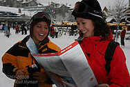 Two young women study Whistler Blackcomb ski map in resort village at Whistler, British Columbia, Canada