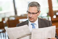 Österreich, Geschäftsmann macht Pause in Restaurant, Zeitung lesend