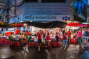 18 SEPTEMBER 2013 - BANGKOK, THAILAND:  People eat at Lek and Rut Seafood stand in the Chinatown section of Bangkok. Lek and Rut Seafood was one of the first street stall restaurants in Bangkok and is more of a pop up restaurant than a street food stall. It has sit down service and full menus, but seating is on the street and sidewalk and food is prepared in portable cookers that are brought out to the street when the restaurant opens. Thailand in general, and Bangkok in particular, has a vibrant tradition of street food and eating on the run. In recent years, Bangkok's street food has become something of an international landmark and is being written about in glossy travel magazines and in the pages of the New York Times.     PHOTO BY JACK KURTZ