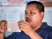 07 AUGUST 2016 - BANGKOK, THAILAND:  An elections worker calls out the votes on a marked ballot in a polling place in Bangkok Sunday. Thais voted Sunday in the referendum to approve a new charter (constitution) for Thailand. The new charter was written by a government appointed panel after the military coup that deposed the elected civilian government in May, 2014. The charter referendum is the first country wide election since the coup. Elections workers counted the votes in the polling places after the polls closed at 16.00.     PHOTO BY JACK KURTZ