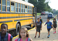 Lee Levine (center), 8 and Eric Chen (2nd from right), 9, walk towards the entrance after exiting their school bus as they arrive for the first day of school Tuesday September 5, 2017 at Newtown Elementary School in Newtown, Pennsylvania. (Photo by William Thomas Cain)
