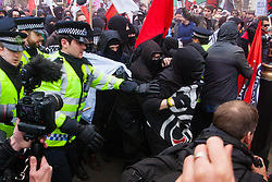 Whitehall, London, April 4th 2015. As PEGIDA UK holds a poorly attended rally on Whitehall, scores of police are called in to contain counter protesters from various London anti-fascist movements. PICTURED: Anti-fascists attempt to surge through police lines separating them from the small PEGIDA rally attended by tow or three dozen men and women, including a contingent of retired Gurkhas.