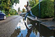 Nederland, Kockengen, 11 sept  2013<br /> In Kockengen zijn ernstige problemen met verzakkingen van de grond. Bij regen staan de straten snel blank en stinkt het naar rioollucht. <br /> Een bewoner kan de voorkant van haar huis niet meer uit vanwege een diepe plas water en moet aan de achterkant ook een mooie sprong maken om zo droog mogelijk bij haar auto te komen.<br /> Foto(c): Michiel Wijnbergh