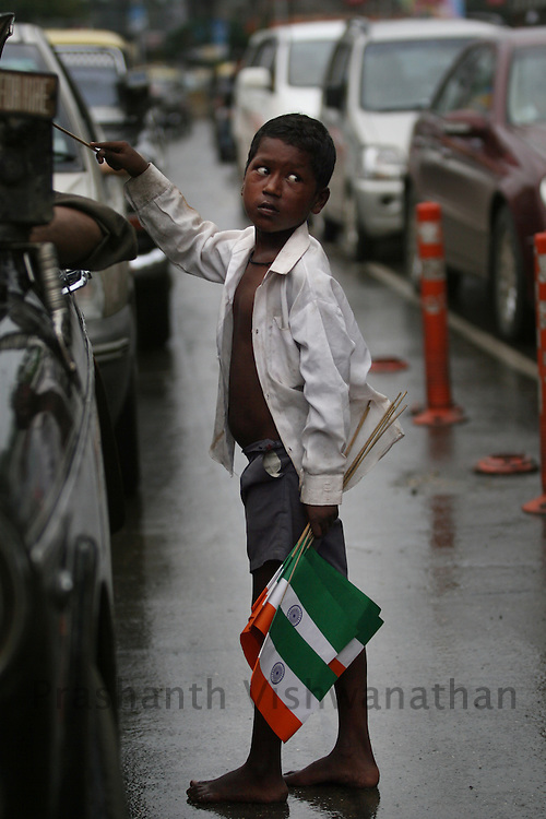 A boy sells Indian flags ahead of India's 60th Independence day on a traffic intersection in Mumbai, August 14, 2007.