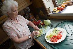 Woman preparing a salad in her kitchen,