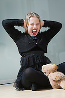 Frustrated young girl covering ears and screaming while sitting on floor