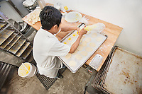 High angle view of a young male baker preparing pastry in bakery
