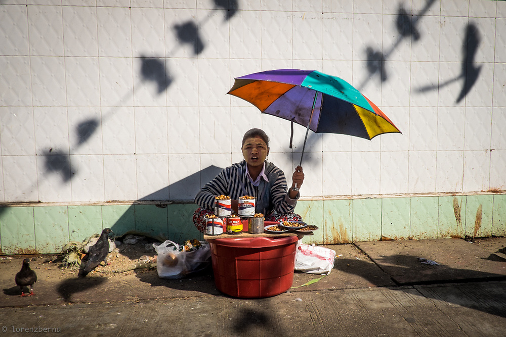 A birds seeds seller is waiting for custumers in a street of Yangon. Feeding birds is one of the practices used by Buddhist worshippers in Myanmar to gain merits and purify his own karma. <br /> Photo by Lorenz Berna