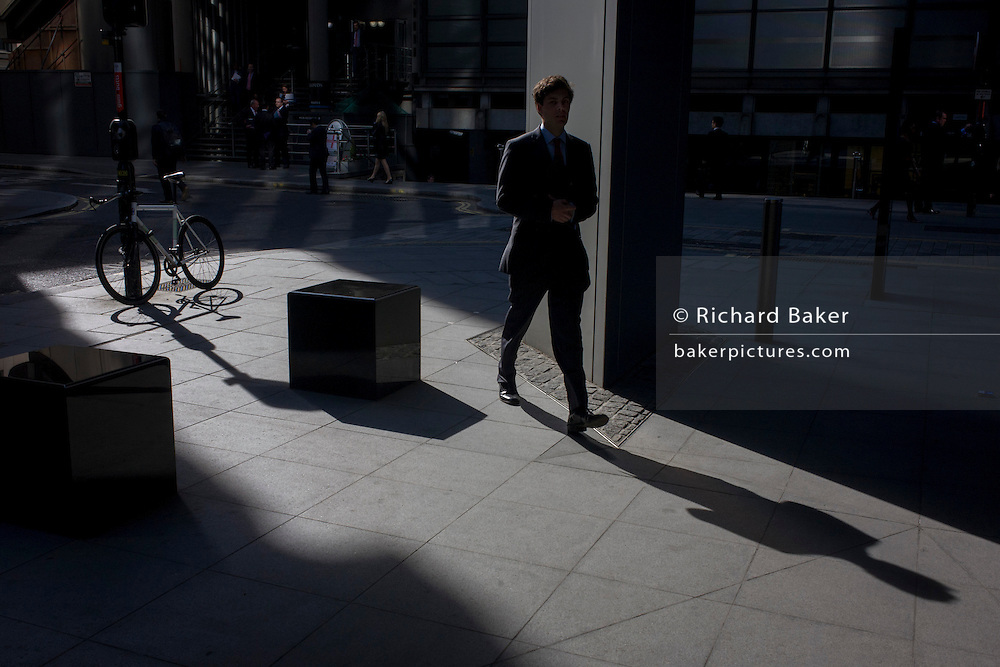 Businessman and locked up bicycle in sunlight corner of a precinct outside a large City of London financial institution in Lime Street.