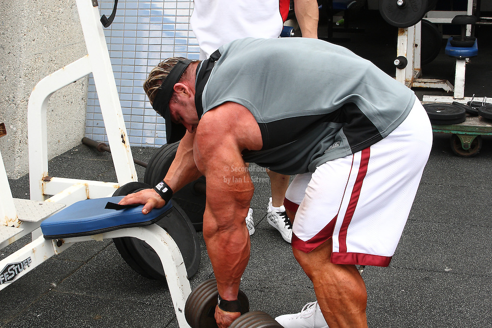 Mr. Olympia,  Jay Cutler doing one arm dumbbell rows, working out in the pit at world famous Muscle Beach at Venice Beach California.