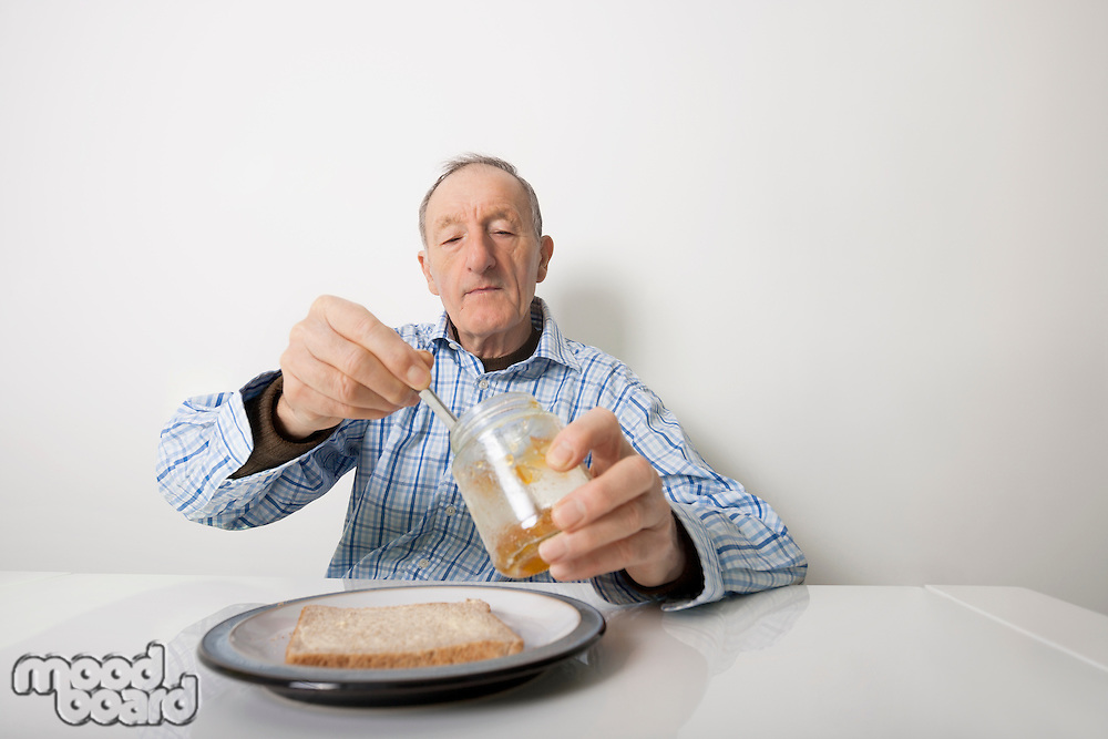 Senior man preparing slice of bread and marmalade at table