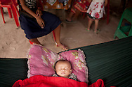A baby sleeps in a hammock beside mother and sister in a small dwelling in Angkor, Cambodia, Southeast Asia