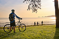 Cyclists on Coast Path at Blackpill at sunrise with Mumbles Head in background<br /> Swansea<br /> South<br /> Cycling<br /> Activities and Sports