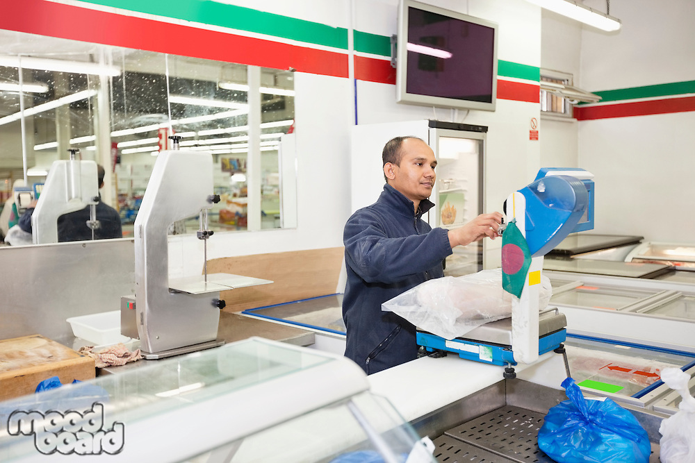 Male worker weighing products in grocery store