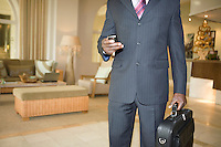 Mid section of Business man holding briefcase and mobile phone