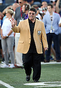 "Former owner of the San Francisco 49ers Edward J. ""Eddie"" DeBartolo Jr. waves while being announced over the public address system as he walks onto the field as a new member of the Pro Football Hall of Fame before the Green Bay Packers 2016 NFL Pro Football Hall of Fame preseason football game against the Indianapolis Colts on Sunday, Aug. 7, 2016 in Canton, Ohio. The game was canceled for player safety reasons due to the condition of the paint on the turf field. (©Paul Anthony Spinelli)"