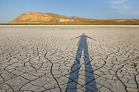 Silhouette of person on patterns of cracked mud on dry lakebed of Harney Lake, Malheur National Wildlife Refuge, Oregon